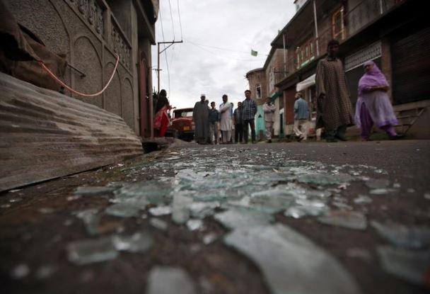 أشخاص يمرون بالقرب من حطام زجاج نافذة بعد اشتباكات وقعت يوم الجمعة بين محتجين وقوات الأمن بسريناجار في صورة التقطت يوم السبت. تصوير: دانيش إسماعيل - رويترز