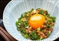 """يشكل """"الناتّو"""" لونا من الطعام يعتمد في الأساس على فول الصويا المتخمر، وغالبا ما يُقدم مع البصل الأخضر والبيض النيء"""