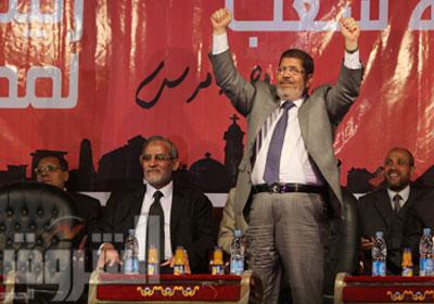 مرسى يحيى مؤيديه وإلى جواره بديع فى المؤتمر الجماهيرى