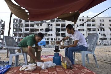 شقيقان يتناولان طعام الإفطار أمام أحد المنازل المدمرة في غزة جراء العدوان الإسرائيلي  <br/>تصوير: «أ ف ب»