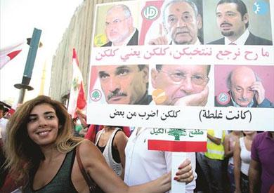 متظاهرة تحمل لافتة ترفض انتخاب السياسيين الحاليين مجددا